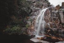Vue sur la petite cascade qui coule de la colline au Portugal en longue exposition — Photo de stock