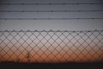 Вид через забор звено цепи к вечернему небу — стоковое фото