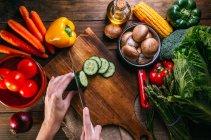 Mãos humanas cortando legumes frescos na tábua de corte de madeira na mesa da cozinha — Fotografia de Stock