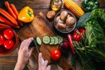 Menschliche Hände schneiden frisches Gemüse auf einem Holzschneidebrett auf dem Küchentisch — Stockfoto