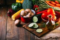 Ассортимент свежих овощей и посуды на деревянном кухонном столе — стоковое фото
