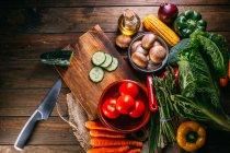 Assortiment de légumes et ustensiles crus frais sur table de cuisine en bois — Photo de stock