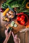 Manos humanas cortar verduras frescas en madera tabla de cortar en la mesa de la cocina - foto de stock