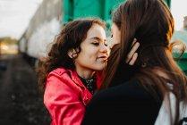 Длинноволосый мужчина обнимает и целует женщину возле поезда — стоковое фото