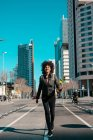 Женщина с афроволосами ходит по улицам большого города — стоковое фото