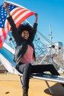 Mujer negra con el pelo afro y una bandera de Estados Unidos celebra el día de la independencia de E.e.u.u. - foto de stock