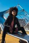 Mujer con pelo afro saltando una diapositiva con gran alegría. - foto de stock