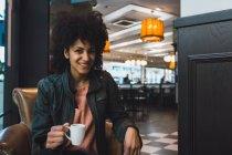 Черная женщина с афроволосами пьет кофе в кофейне — стоковое фото