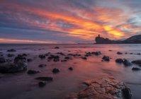 Ciel clair et nuageux en soirée sur la mer majestueuse et le rivage rocheux — Photo de stock