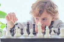 Niño sosteniendo figura en tablero de ajedrez - foto de stock