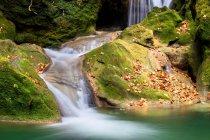 Бирюзовая вода в водохранилище с водопадом и зелеными скалами, Наварра — стоковое фото