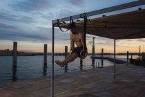 Спортивні чоловік, балансуючи на Кільця гімнастичні на набережній у місті вечір — стокове фото