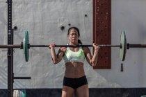 Femme musculaire concentrée soulevant haltère dans la salle de gym — Photo de stock