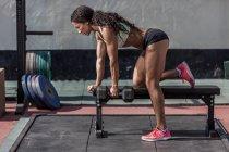 Концентрированная мускулистая женщина тренируется с гантелями в спортзале — стоковое фото
