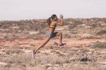 Femme sportive ethnique courant dans le désert ensoleillé — Photo de stock
