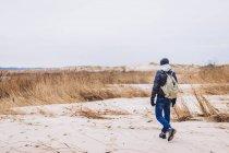 Vue arrière du gars en veste et chapeau avec sac à dos marchant sur la terre de sable entre l'herbe sèche — Photo de stock