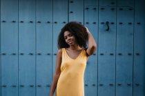 Femme noire joyeuse en robe jaune posant sur la rue — Photo de stock