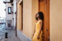 Pensive black woman in yellow dress leaning on door on street — Stock Photo