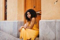 Magnifique femme noire en robe assise sur le porche sur la rue et regardant la caméra — Photo de stock