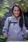 Donna felice con bastoni da trekking nella foresta — Foto stock