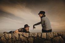 Couple élégant appuyé sur les rochers et le ciel merveilleux avec des nuages — Photo de stock
