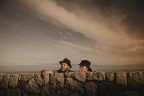 Élégant couple élégant penché sur des roches et un ciel merveilleux avec des nuages — Photo de stock