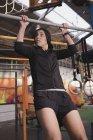Jeune femme sportive mince en vêtements de sport faire des exercices pull up sur barre horizontale dans la salle de gym — Photo de stock