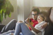 Веселый мечтательный мужчина и женщина лежат на диване и читают брошюру — стоковое фото