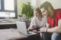 Smiling young man and woman sitting on couch and browsing laptop in living room — Stock Photo