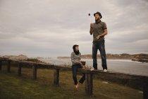 Jeune homme en chapeau jonglant balles près de femme élégante en chapeau avec tambour éthique assis sur le siège près de la côte de la mer et ciel nuageux — Photo de stock