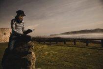 Елегантна жінка в шапці сидить на сидінні на березі біля махаючи морем. — стокове фото