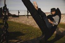 Вид на елегантну жінку в кришці, що читає обсяг і сидить на абстрактному пам'ятнику біля будівництва на узбережжі моря — стокове фото