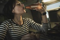 Young brunette woman drinking water from bottle near cooker in mobile home — Stock Photo