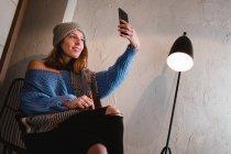 Mujer joven en suéter de punto con bufanda y sombrero tomando selfie en el teléfono inteligente y sentado en la silla cerca de la pared y la lámpara en la habitación — Stock Photo