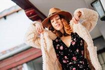 Позитивная привлекательная молодая женщина в теплой одежде и шляпе смотрит вдаль и стоит рядом с домом и забором — стоковое фото