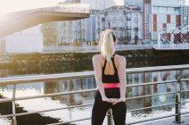 Vue arrière de la femme en vêtements de sport étirant les mains sur le quai près de l'eau dans la ville par temps ensoleillé — Photo de stock
