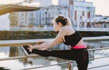 Жінка в спортивному одягу розтягує ноги на набережній біля води в місті в сонячний день — стокове фото