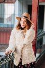 Позитивная привлекательная молодая женщина в теплой одежде и шляпе смотрит в камеру и стоит рядом с домом и забором — стоковое фото