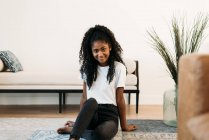 Young black teenage girl sitting in a rug — Stock Photo