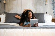 Schwarzes Teenager-Mädchen mit lockigem Haar lächelt in die Kamera und benutzt Tablet und Kopfhörer auf dem Bett — Stockfoto