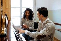 Junger Mann lernt Klavierspielen in der Nähe schwarzer Frau, die im Musikstudio unterrichtet — Stockfoto