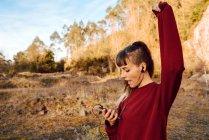 Joven hipster mujer con la mano subió escuchando música en el teléfono móvil y bailando en la naturaleza - foto de stock