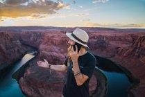Hombre en sombrero hablando en el teléfono móvil, mientras que de pie contra el cañón y el río durante el atardecer en la costa oeste de EE.UU. - foto de stock