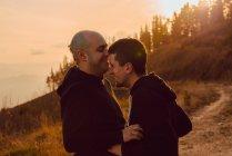 Ridere coppia omosessuale abbracciando sul sentiero in montagna nella giornata di sole — Foto stock