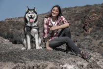 Cheerful young woman sitting near husky on rock in nature — Stock Photo