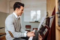 Bonito homem tocando piano durante o ensaio em estúdio de gravação . — Fotografia de Stock
