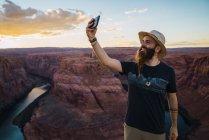 Beau barbu souriant et prenant selfie tout en se tenant contre le magnifique canyon et la rivière pendant le coucher du soleil sur la côte ouest des États-Unis — Photo de stock