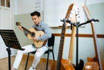 Красивый человек играет на гитаре во время репетиции в студии звукозаписи . — стоковое фото