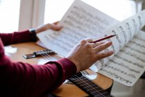 Crop man hands with sheet music playing guitar during rehearsal in studio. — Stock Photo