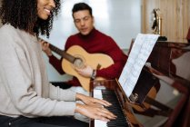Side view of the young black woman playing piano near man playing guitar in music studio — стоковое фото